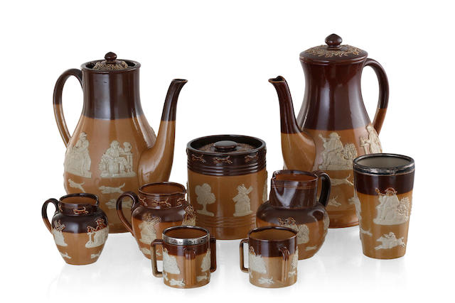 A Collection of Royal Doulton brown salt glaze pottery with applied relief decoration comprised of two coffee pots, a tobacco jar, three milk jugs, a silver rimmed beaker, Chester 1917