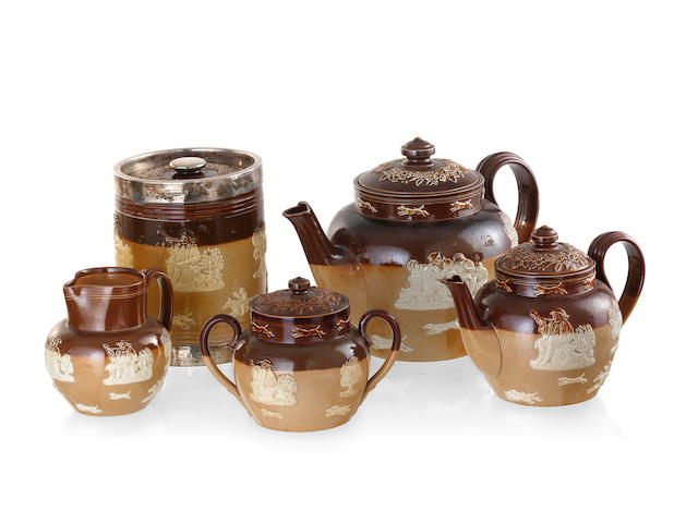 A Collection of Doulton Lambeth brown salt glaze pottery with applied relief decoration comprising a large teapot, a small teapot, a sugar bowl, a cream jug and a silver rimmed tobacco jar, London 1898