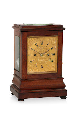 A Rosewood case bracket clock by T Jones Sydney, the top with glass panel and stepped pediment above a black enamel Roman chapter and signature T Jones Sydney on a finely engraved floral ground, the movement with twin chair ....