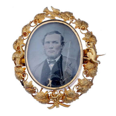 An Australian gold portrait brooch by Lamborn & Wagner Londsdale Street, Melbourne, circa 1860, with a photographic print of gentleman, the reverse with a young girl, in a gold frame flanked by an emu and kangaroo and a border of vine leaves