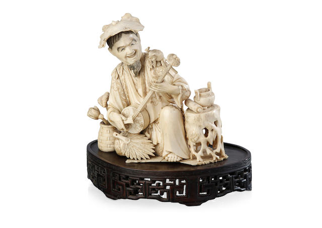 A Japanese ivory carving of a kneeling musician playing a shamisen