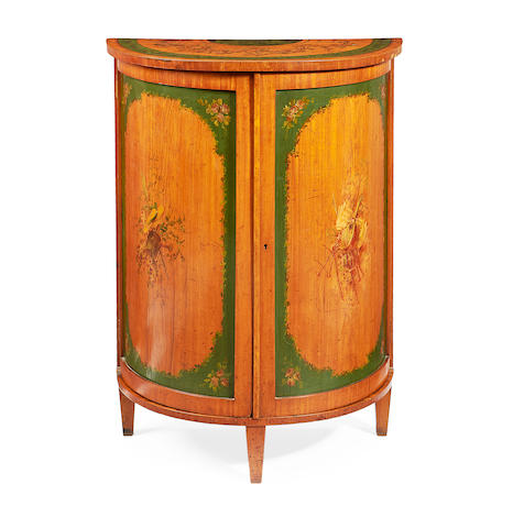 An Edwardian satinwood and polychrome decorated demi-lune side cabinet in the Sheraton revival style