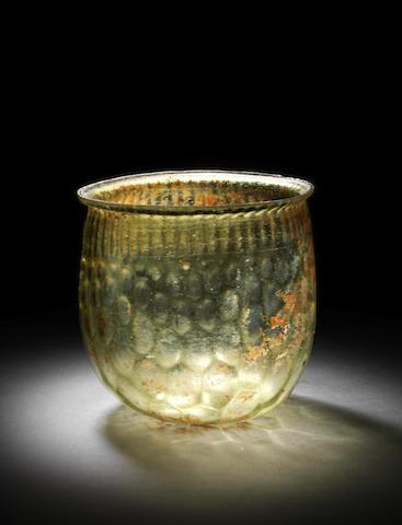 A Roman yellowish-green glass honeycomb cup