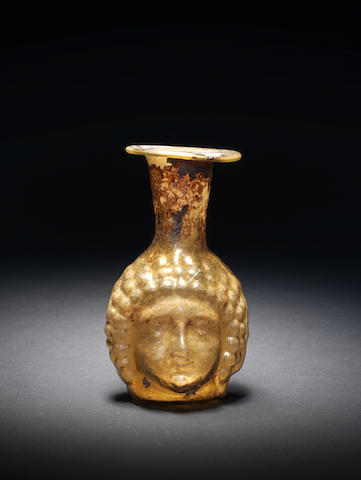 A Roman pale yellow glass janus head flask