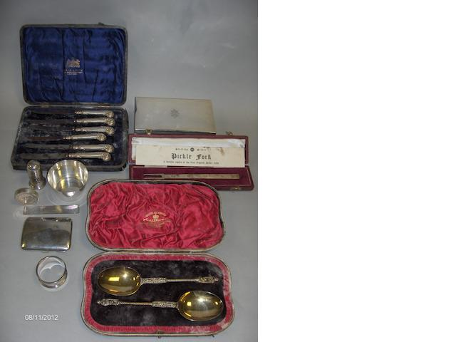 A cased pair of repro apostle spoons, a Manners replica pickle fork, a cigarette box, six tea knives, a cigarette case, a bun pepper, a small bowl, a silver mount, a napkin ring and a silver medallion Gresham House Estate.