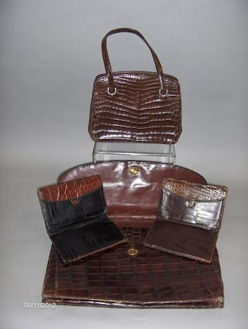 A crocodile skin briefcase, a handbag and two wallets.