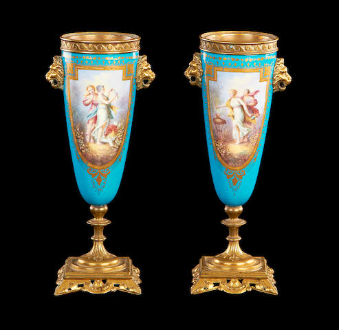 A pair of late 19th century Sevres style porcelain and gilt brass mounted urns