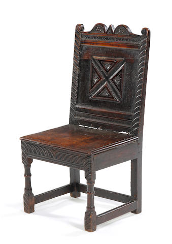 An oak single chair panelled back with carved decoration, possibly Elizabethan