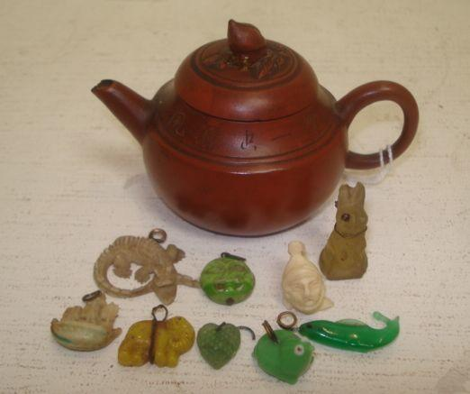 A collection of nine miniature Japanese carved objects, including animals and mask and a miniature terracotta compressed baluster teapot, the cover with bud finial. (10)