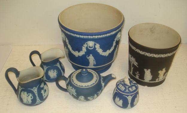 A collection of five pieces of Wedgwood blue jasper dip, a jardiniere, graduated pair of jugs, teapot, jar and cover and a black jasper dip jardiniere. (6)