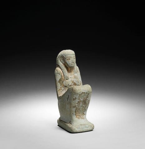 An Egyptian blue seated figure with erased inscription and traces of gild