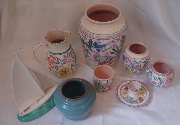A large Poole pottery vase, circa 1930, in the bluebird pattern, 24cm, a Poole Pottery yacht model in blue and cream, 26cm, five pieces of Poole Pottery in traditional flowers pattern and a squat vase in a speckled blue glaze, 12cm.
