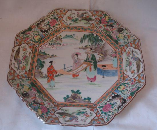 A large late 19th Century Chinese famille decorated charger, octagonal wavy edge form with central panels of figures lookinat a scroll with flower an bird panel borders, 43cm.