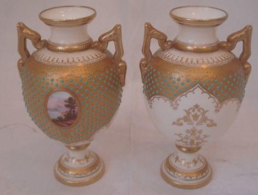 A good pair of Coalport cabinet vases, of twin handled ovoid form painted with oval landscape panels on a gilt and turquoise 'jewelled' ground, 15cm.