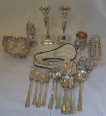 A pair of cased silver grape shears, by Mappin & Webb, 1926, panelled sugar caster in the George I style by Mappin & Webb, 1925, a breakfast toast rack with six arched wire division, on ball feet, Sheffield 1914, a pair of filled candlesticks on square shaped bases, 20.5cm, high, Chester 1913, an embossed and pierced lozenge shaped footed bon bon dish, Sheffield 1909, an embossed baluster christening mug, 1890, a trefoil shaped three part cruet, 1899, and eleven pieces of rat tail flatware, 42ozs weighable excluding candlestick and cruet jars.