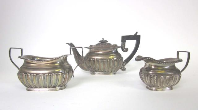 A  silver three-piece bachelor's tea service by Walker & Hall, Sheffield 1901 together with a cased silver sugar bowl and sifter spoon, by Robert Harper, London 1876, and a cased silver caster, by Martin Hall & Co, Sheffield 1904