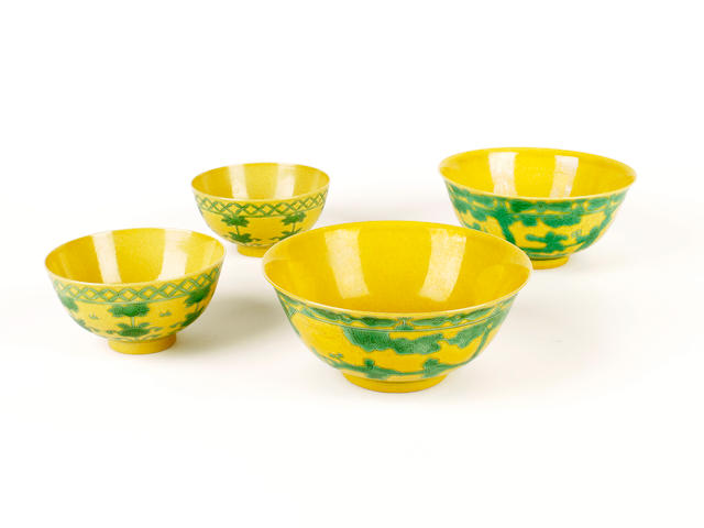 A pair of green and yellow enamelled bowls and a smaller pair, Yongzheng and Kangxi six character marks but later