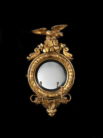 A Regency convex giltwood and gesso girandole wall mirror, the convex mirrored plate with a rope border and eagle and dolphin surmount with rockwork and set with a pair of scrolling candelabrum – Height 91cms