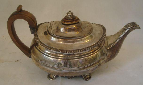 A George IV silver oval shaped teapot, with gadrooned rim and shell capped spout on panel feet with fruitwood handle and lift, 1826, 20ozs gross.