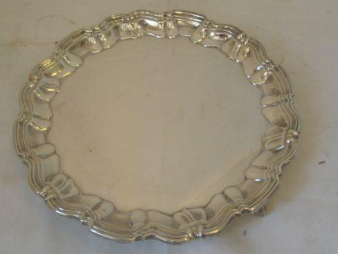 A silver salver, circular, with scroll cast border raised on three paw feet, by Goldsmiths & Silversmiths, 1932, 21ozs.