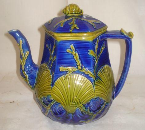 A Wedgwood Majolica hexagonal panelled coffee pot, moulded with scallops, shells and weed, glazed in olive on a dark blue ground, impressed marks, 21cm.
