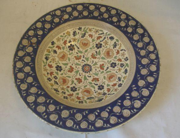 A large continental circular charger, possibly Thun, Sgrafitto decorated with a central panel of flowers within a scroll decorated border, 38.5cm diameter.