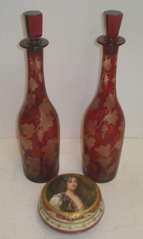 A pair of Bohemian ruby cased glass decanters, etched with fruiting vines, 35cm, and a Dresden circular porcelain box, the pull off cover painted with clementine, signed, 13cm. (3)
