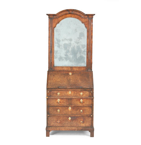 An early 20th century walnut bureau cabinet in the George I style