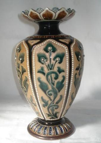 A Doulton Lambeth stoneware vase, by Florence Barlow, of baluster form with overlapping panelled rim, the body with stylised scrolling foliates with beaded frames glazed in olive black and blue, incised and impressed marks, 27cm.