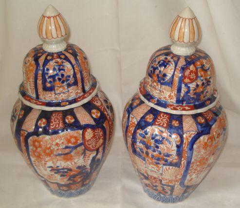 A pair of Japanese Imari vases and covers, circa 1900, with fluted ovoid bodies with domed covers painted in typical colours with panels of foliage on a striped ground, 40cm.