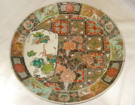 A Japanese Imari decorated charger, well painted in blue, red and green with insects, flowers and birds in a panelled ground, 45cm.