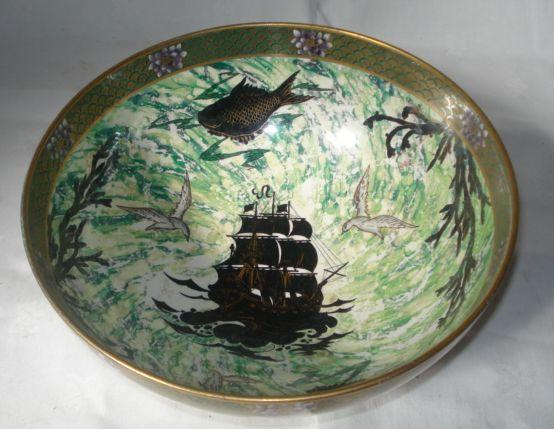 A Malingware earthenware bowl, decorated with silhouettes of boats, fish and weed on a green marbled lustre ground, 26.5cm.