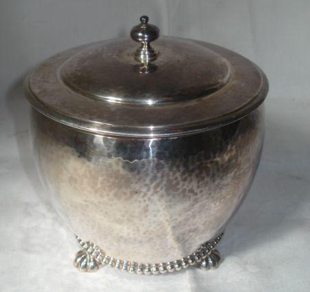 A silver drum shaped biscuit box, with hinged cover and beaded base on gadrooned bun feet, all-over spot hammered decoration, by Goldsmiths & Silversmiths Company, 1928, 15ozs, 13cm.
