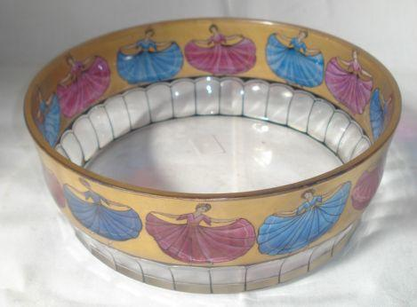 A German painted glass bowl, possibly Moser, circular, decorated with a band of curtsying ladies on a gilt ground, black line cut base, 20.5cm diameter.