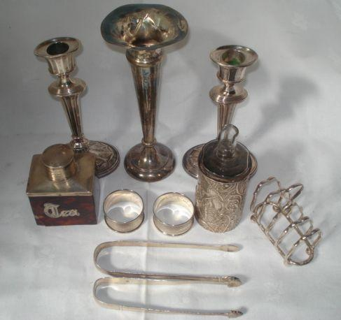 A pair of filled oval shape candlesticks, by George Unite 1901, 17cm, repaired, a trumpet spill vase on filled base, repaired, a silver mounted tortoiseshell veneered tea caddy applied 'Tea' Chester 1904, two pairs of George III feather edge sugar tongs, two napkin rings, toast rack, and a silver bottle sleeve, 1901.