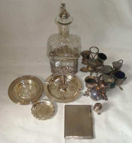 A continental engraved spirit decanter, with silver cage base and cherub finial, import marks for Chester 1906, a pair of dishes with central Tudor Rose, 12cm, 1961, a heavy rectangular engine turned cigarette case, 1945, four small coasters, three plated thistle cruets and a plated egg pepperette and a Presentation silver ashtray with standing figure by Elkington & Co.
