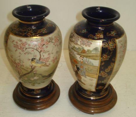 A pair of Japanese Satsuma inverted baluster vases, Meiji, painted with figure, bird and flowering tree panels, wood stands, 16cm. (4)