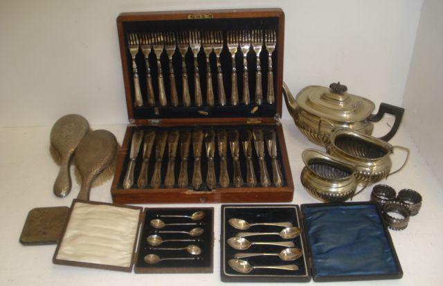 A pair of George V silver backed spot hammered hair brushes,Chester 1922 and the following silver, pair of Victorian napkin rings, another, cigarette case, cased 'bean' end demi tasse, case of five Old English pattern teaspoons, also an electroplate tea service and a walnut cased set of twelve pairs of fish knives and forks.