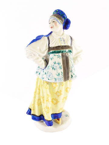 A Russian porcelain figure of a woman in traditional costume