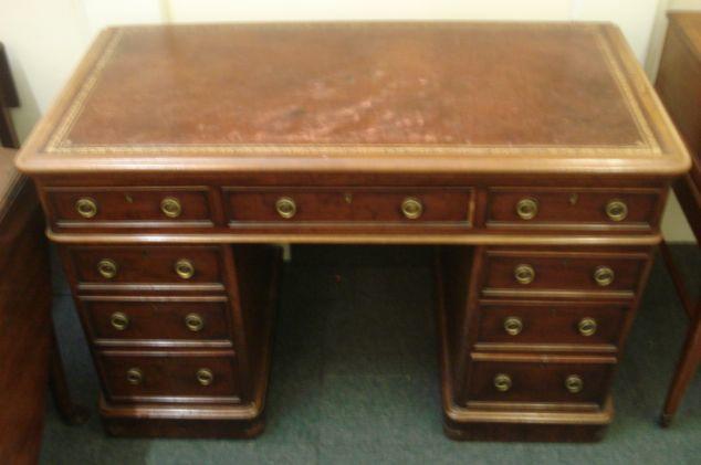 A Victorian mahogany pedestal desk, the inset top over an arrangement of nine drawers on pedestal base, 122cm.