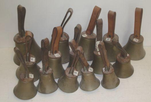 A graduated set of fifteen brass bells, with leather mounts and strap handles.