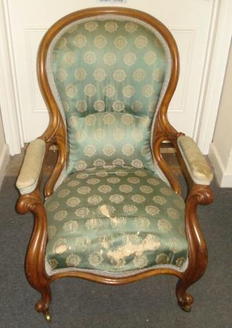 A Victorian walnut frame armchair, with upholstered back, armrests and stuff over seat, on cabriole legs and castors.