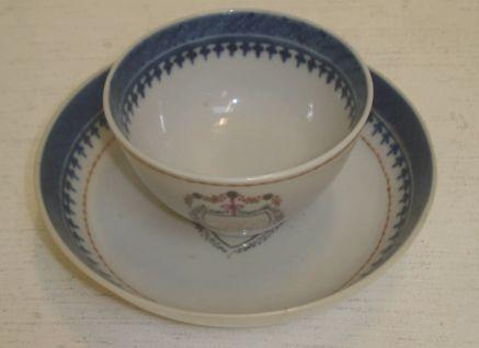 A Chinese Export porcelain tea bowl and saucer, painted with initials in a ribbon tied floral bordered shield cartouche.