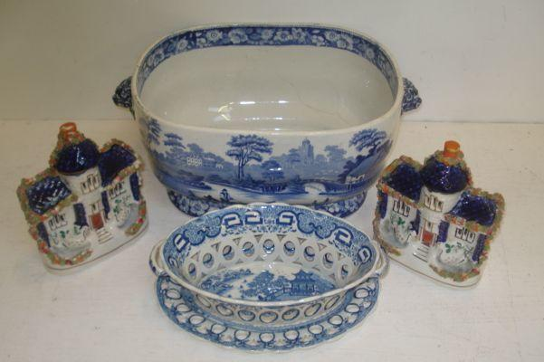 An early 19th Century English pearlware oval two handled dessert basket and stand, printed with a Willow pattern scene, similar period blue transfer printed soup tureen, lacking cover, and a pair of Staffordshire frit decorated cottages. (5)