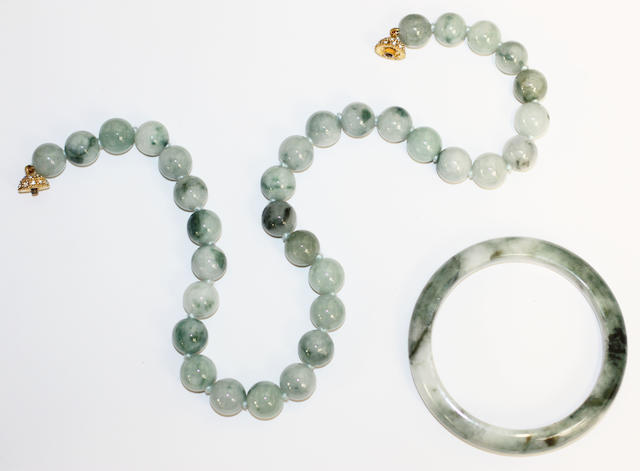A jade bead necklace and bangleThe necklace of uniform beads to a spherical white stone set twist action clasp, (jade untested for treatments or enhancements), necklace length 49.5cm, bangle inner diameter 6cm. (2)