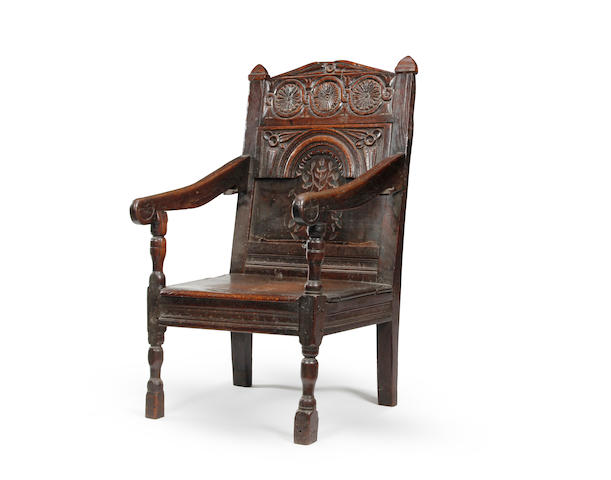 A mid-17th century oak panel back open armchair  Of unusual design, circa 1640-60