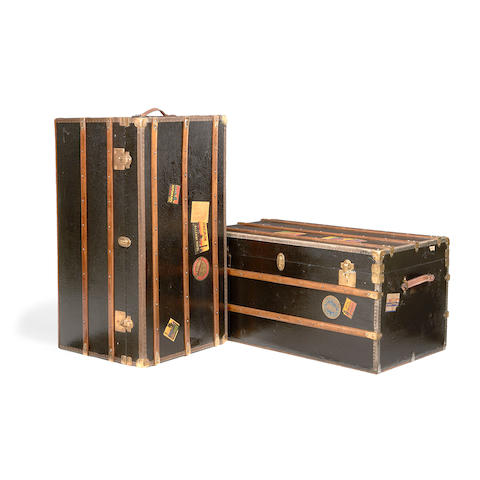 A near pair of early 20th century black canvas and beech slatted steamer trunks