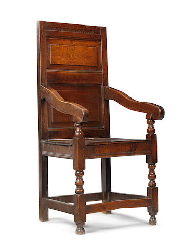 A late 17th century oak panel back open armchair