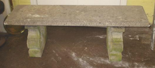 A stone garden bench, the moulded rectangular seat on 'C' scroll carved ends, 145cm.
