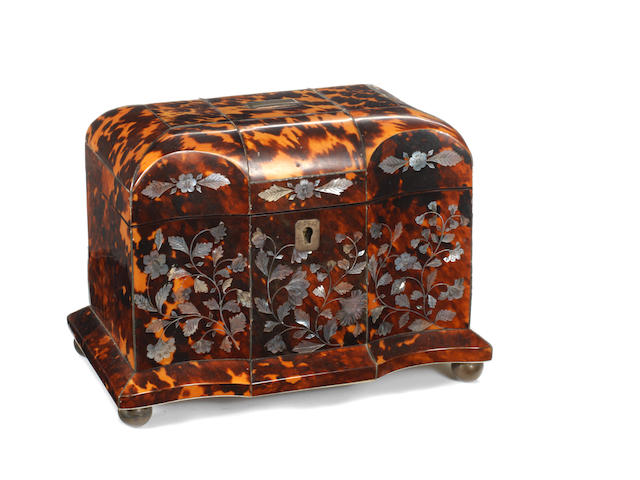 An early 19th century Tortoiseshell tea caddy, of serpentine breakfront form, the whole raised on compressed bun feet and decorated with mother of pearl floral inlay – Width 17cms, Depth 11.5cms, Height 14cms